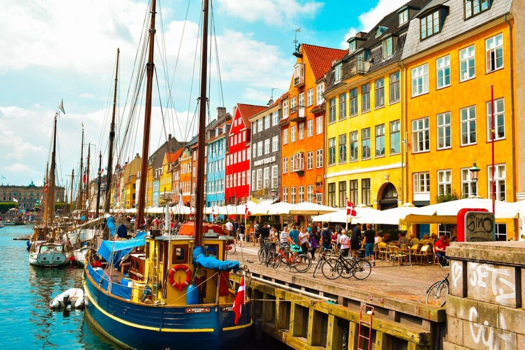 A photo of Copenhagen, Denmark. Colourful houses are seen by the river, with small boats docked.